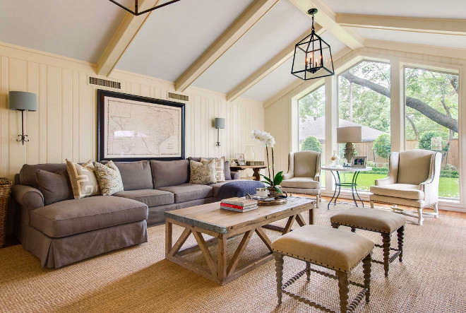 Living room with sisal rug, vaulted ceiling, floor to ceiling window and neutral decor. #livingroo Elizabeth Garrett Interiors.