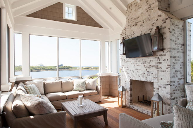 Screened-in porch. The screened-in porch feels cozy thanks to its distressed white brick fireplace and warm Ipe wood floors. Screened-in porch with fireplace and TV. Screened-in porches. Screened-in porch Ideas. Screened-in porch. #Screenedinporch #Screenedinporchfireplace #Screenedinporchtv #Screenedinporchflooring #Screenedinporchfurniture #Screenedinporchview #Screenedinporchwindows T.S. Adams Studio, Architects
