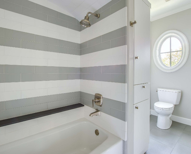 Bathroom striped tiles. Bathroom features white and gray subway tiles alongside a built-in shelf. #bathroom #stripedtiles #subwaytiles Elizabeth Garrett Interiors.