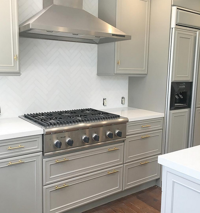Dovetail SW 7018 by Sherwin-Williams. Dark grey kitchen cabinets painted in Dovetail SW 7018 by Sherwin-Williams with brass hardware and herringbone marble tile backsplash. #DovetailSW7018SherwinWilliams. Eye for the Pretty.