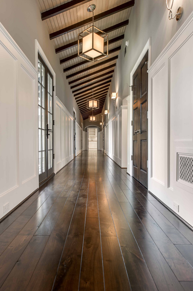 Hall Lighting. Hall. Lighting. Long hall features a sloped ceiling, dark stained wood beams and caged Lanterns with Paper Shades. Hall also features top part of walls painted gray and lower walls clad in board and batten. #hall #halllighting #lighting Elizabeth Garrett Interiors.
