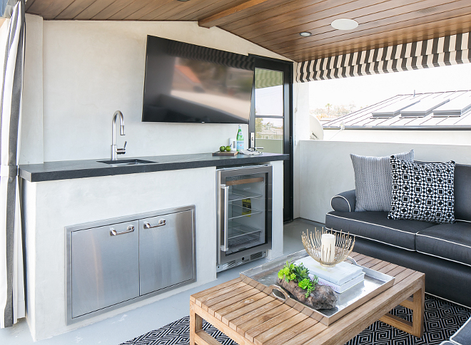 The roof deck features stained paneled vaulted ceiling over a kitchenette boasting a flatscreen tv over a sink and stainless steel cabinets next to a glass-front beverage fridge. Patterson Custom Homes