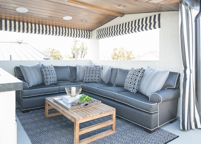 Deck furniture ideas. The deck also features a gray roll-arm sectional with white piping facing a teak coffee table atop a black and white diamond print rug. #deck #outdoorfurniture #outdoors Patterson Custom Homes