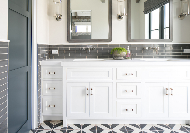 The master bathroom features white dual washstand fitted with his and her sinks positioned under wall-mount sinks and gray distressed mirrors illuminated by nickel and glass sconces from Circa Lighting. Patterson Custom Homes