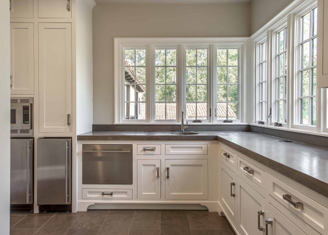 Butler's pantry. Large butlers pantry features creamy white shaker cabinets fitted with a pull-out dishwasher drawer topped with gray countertops situated under windows next to a stainless steel microwave stacked over stainless steel mini fridges. #butlerspantry #largebutlerspantry Elizabeth Garrett Interiors.