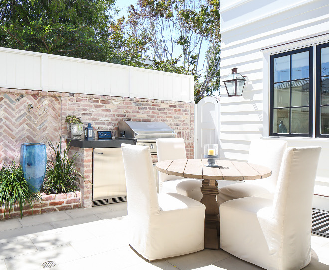 This courtyard features concrete paver flooring, exposed brick walls and white fencing on top to add extra privacy. Patterson Custom Homes. Interiors by Trish Steele, Churchill Design.