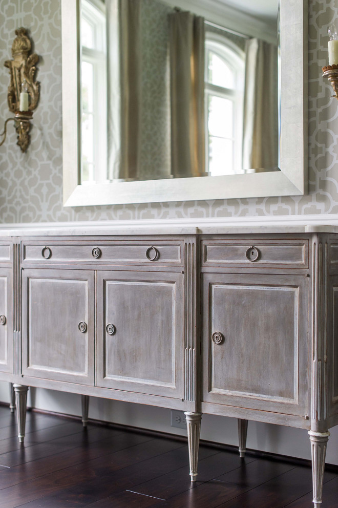 French dining room. French dining room features upper walls clad in gray trellis wallpaper and lower walls clad in wainscoting lined with a gray distressed French sideboard topped with white marble under a gray beveled mirror flanked by gold French sconces. #Frenchdiningroom #frenchinteriors #furniture Elizabeth Garrett Interiors.