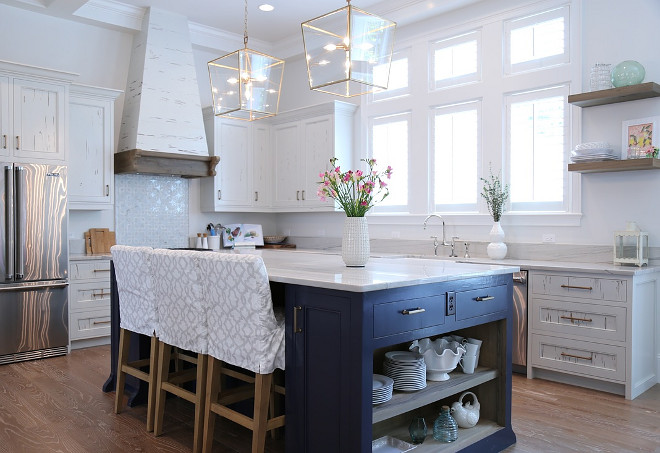 White kitchen with reclaimed cabinets and blue island. Reclaimed white kitchen cabinets with navy blue island and Bianco Macaubus Quartzite countertop. #whitekitchen #reclaimedwhitekitchen #reclaimedwhitecabinet #blueisland #bluekitchenisland #BiancoMacaubusQuartzite Old Seagrove Homes.