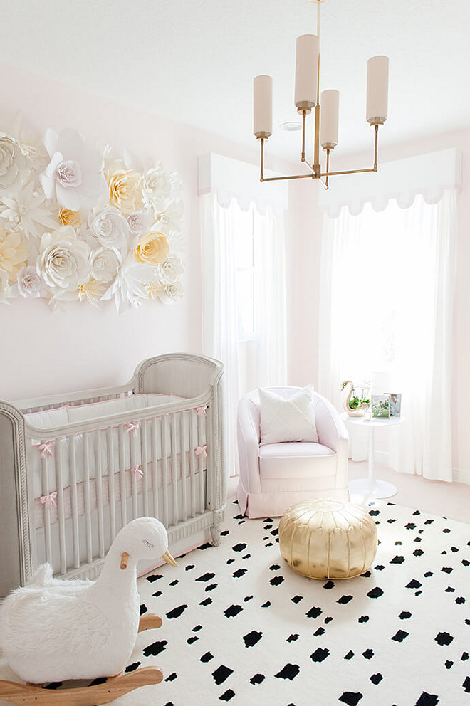 Baby Girl Nursery with soft blush tones and charming swan décor and a paper flower wall. Baby Girl Nursery Design. Blush paint color is Benjamin Moore 2173-70 Gentle Butterfly. #BabyGirl #Nursery #BabyGirlNursery #softblushtones #blushpaintcolor Interiors by Luxe Report Designs.