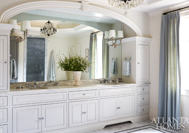 Arched Bathroom Cabinet. His and her sinks with an arched frame. The designer sourced a pair of shaded sconces from Progressive Lighting and had them installed directly onto the mirror to help reflect and spread light throughout the room. Amy Meier for Atlanta Homes & Lifestyles.