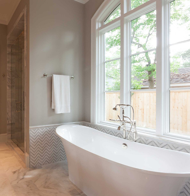 Bathroom features a bathtub nook with upper walls painted gray and lower walls clad in white and gray marble chevron tiles filled with a freestanding tub and a vintage style hand-held tub filler placed under windows. Elizabeth Garrett Interiors