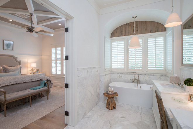 Bathroom. Adding texture to bathrooms. In the bathroom, the arch above the window features cypress planks with a weathered oak stain. The master bedroom ceiling is wallpapered in Phillip Jeffries grasscloth. #bathroom #texture Interiors by Courtney Dickey of TS Adams Studio.