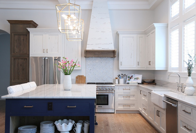 Blue and white kitchen. Kitchen with white cabinets and blue island. Countertop is Bianco Macaubus Quartzite. #blueandwhitekitchen #whiteandbluekitchen #blueandwhite #kitchen #interiors  Old Seagrove Homes.