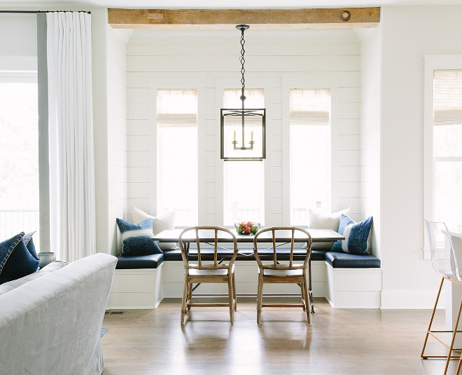 Breakfast nook banquette with reclaimed wood ceiling beams and white shiplap walls. Breakfast nook banquette with reclaimed wood ceiling beams and white shiplap walls. Kate Marker Interiors.