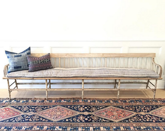 Foyer with extra long vintage bench with vintage pillows and vintage rug. #Foyer #vintagefurniture #vintagerug #vintagedecor #vintageinteriors #vintagepillows #vintagebench #wainscoting Amber Interiors