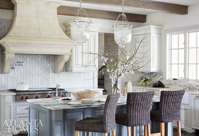 Kitchen. The kitchen juxtaposes varying textures rather than contrasting colors. The carrara marble backsplash, laid in herringbone pattern next to the Limestone hood, wooden beamed celing, and veiny Vermont marble countertops, bring a soft, subtle contrast to the space. Kitchen Limestone Hood & Herringbone Backsplash #kitchen. Amy Meier for Atlanta Homes & Lifestyles.