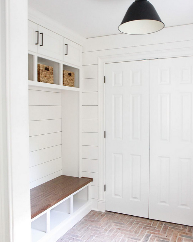 Mudroom brick flooring and shiplap walls. The designer used old Chicago bricks for the floor. Mudroom Paint Color: Farrow and Ball Wimborne White. #mudroom #brickflooring #herringbonebrick  Park & Oak Design.