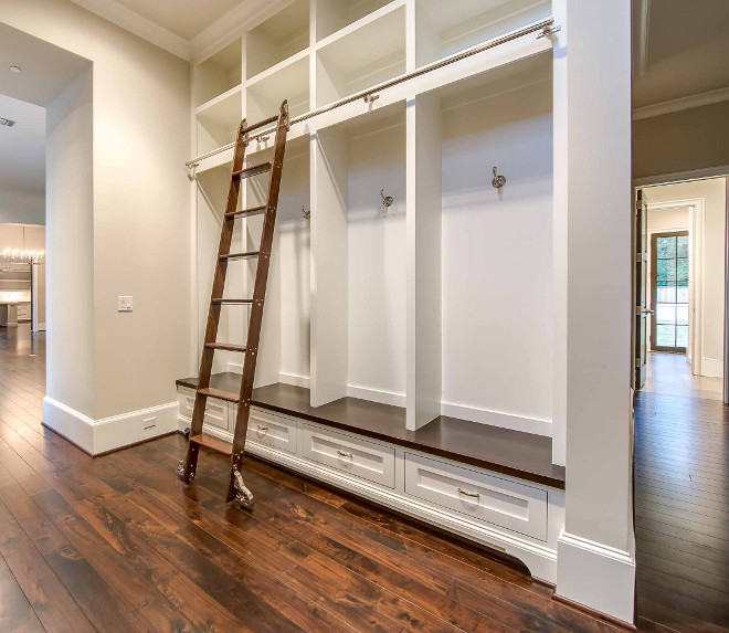 Mudroom ladder. Mudroom features a full wall fitted with built-in boasting individual lockers lined with a ladder on rails. #Mudroom #ladder #mudroomladder #mudrooms Elizabeth Garrett Interiors.