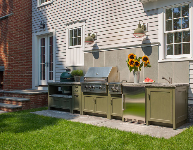 Outdoor kitchen with built-in cabinets, outdoor lighting and stone backsplash. Siemasko + Verbridge