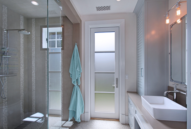 Bathroom. Guest bathroom featuring walk-in shower and paint by Benjamin Moore on cabinets and Barn door. Second door leads out to outdoor shower and gorgeous vegetable garden. #bathroom Patterson Custom Homes. Interiors by Trish Steele of Churchill Design.