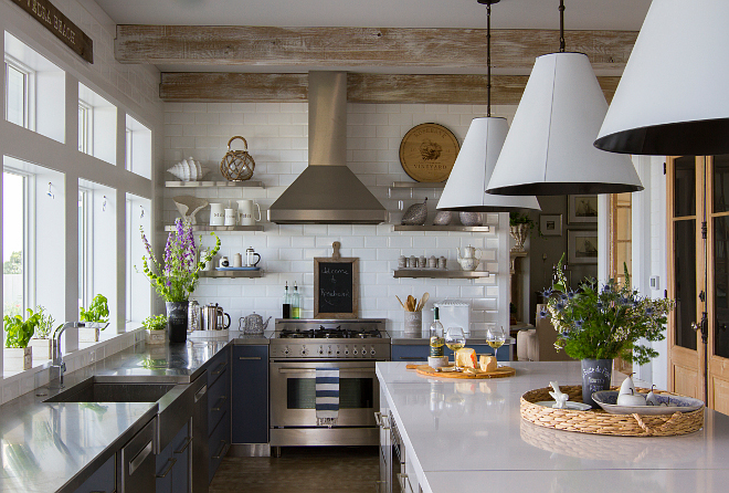 Rustic beach house kitchen with stainless steel perimeter countertop and white quartz kitchen island countertop. Whitewashed ceiling beams and floating shelves flank a stainless steel hood against white subway tile backsplash. Island countertop is White Zeus Quartz. #kitchen #rustickitchen #rusticinteriors #modernrustic #kitchenideas #kitchens
