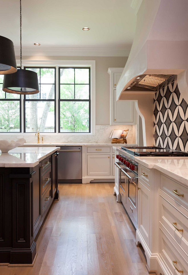 White kitchen with dark island and white oak hardwood floors. Elizabeth Garrett Interiors
