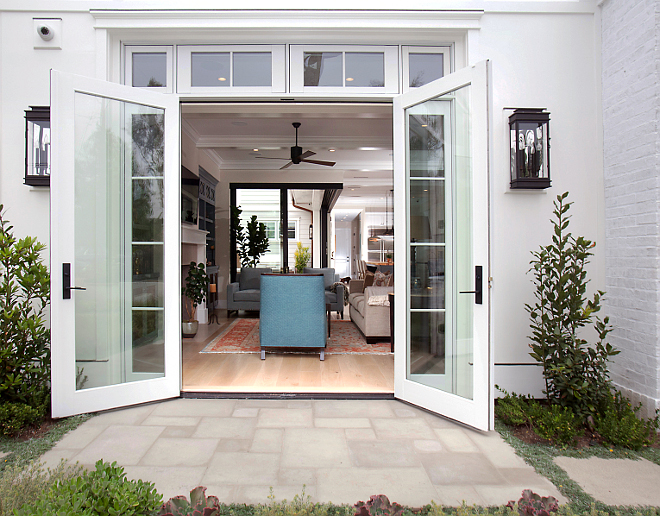 "Famrily room French Doors. Take a peek into the great room through these gorgeous french doors made by JeldWen. Wall-mounted lanterns are Troy Lighting ( 11""W, 24""H) in hand-forged iron. Entry includes white washed pacific stone pavers laid in an ashlar pattern. #FrenchDoors #FamilyroomDoors #Familyroom"