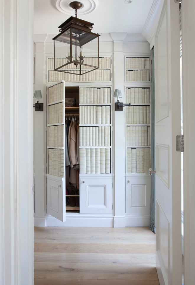 Entry built-in closet. The foyer features cabinet doors with faux ceramic books and sconces. The cabinet conceals a hidden closet. #foyer #entry #entryway #closet Lighting is Circa Lighting's Honore Hanging Lantern. Hayburn & Co.