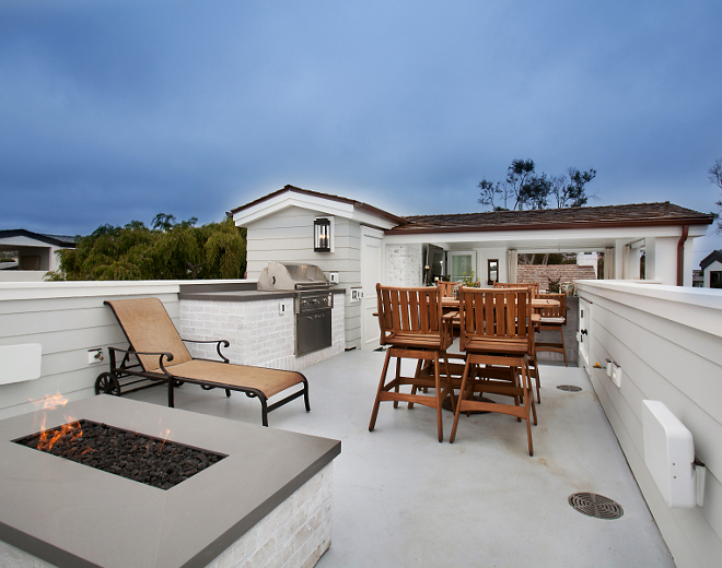 This roof deck is the perfect place to unwind on a summer night! The fire pit and built in barbeque are both made up of the same white brick used on the home's exterior and topped with neolith lava stone slabs. Roof Deck Ideas. Patterson Custom Homes