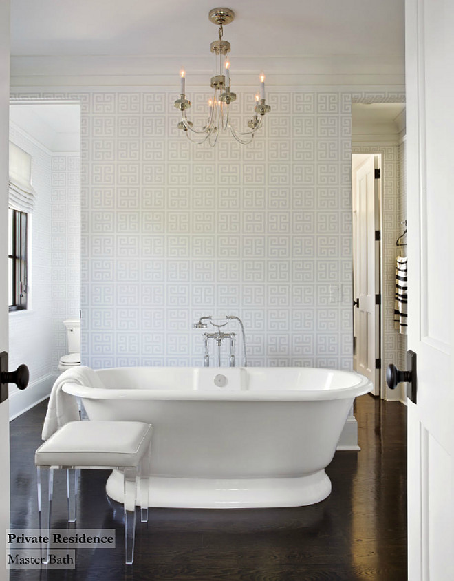 Bathroom. Fabulous bathroom with Jonathan Adler Greek Key Wallpaper in White. This bathroom also features a glass and polished nickel chandelier over freestanding bathtub with floor-mounted tub filler paired with upholstered lucite stool. Notice the dark stained oak wood floors. #bathroom #woodfloors #hardwood #bathrooms #flooring TS Adams Studio Architects. Traci Rhoads Interiors.