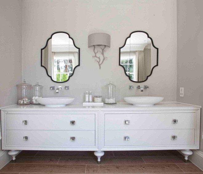 Bathroom cabinet. This bathroom features double vanity unit with counter top sink and wall mounted faucets. Hayburn & Co.