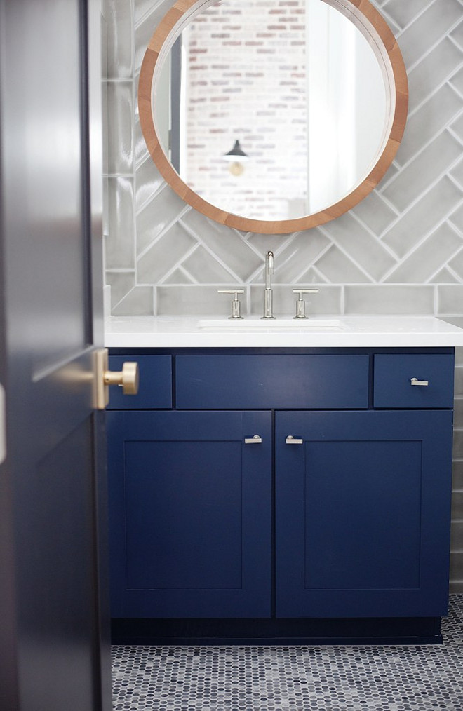 Bathroom. Transitional Blue and gray bathroom boasts a round mirror lining a glossy gray chevron tile backsplash placed above a bold blue cabinet with white quartz countertop. #Bathroom #Transitional #interiors #bluecabinet #whitequartz E Interiors