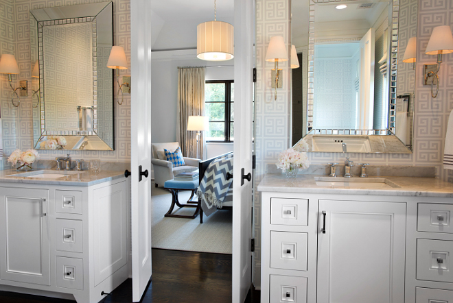 Bathroom. This master bathroom looks even more elegant with these bi-fold doors and the dark hardwood floors. Large beveled mirrors are flanked by Waterworks Blue Note Wall Mounted Single Arm Sconces with Cone Shades over white vanities with white carrara marble countertops. #bathroom #vanity #carrara #marble #hardwood #flooring #sconces TS Adams Studio Architects. Traci Rhoads Interiors.