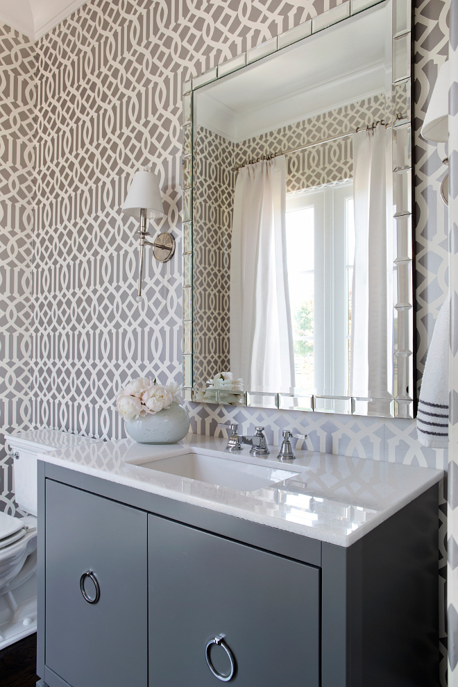 Gray Powder room. This gray powder room features Kelly Wearstler Imperial Trellis Wallpaper in Charcoal. A pair of Waterworks Newell Single Arm Sconces with Cone Shades is placed over a dark gray vanity with polished nickel ring pulls and white marble countertop. #gray #powderroom #bathroom #vanity #wallpaper #graybathroom #graypowderRoom TS Adams Studio Architects. Traci Rhoads Interiors.