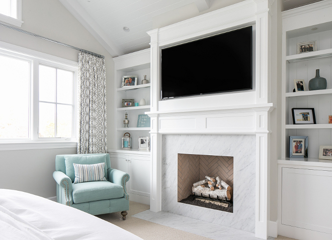 Bedroom fireplace. The master bedroom features a classic white marble fireplace surround with white bookshelves cabinetry on both sides. #bedroom #masterbedroom #fireplace #bookshelves #bookcase #cabinet Churchill Design