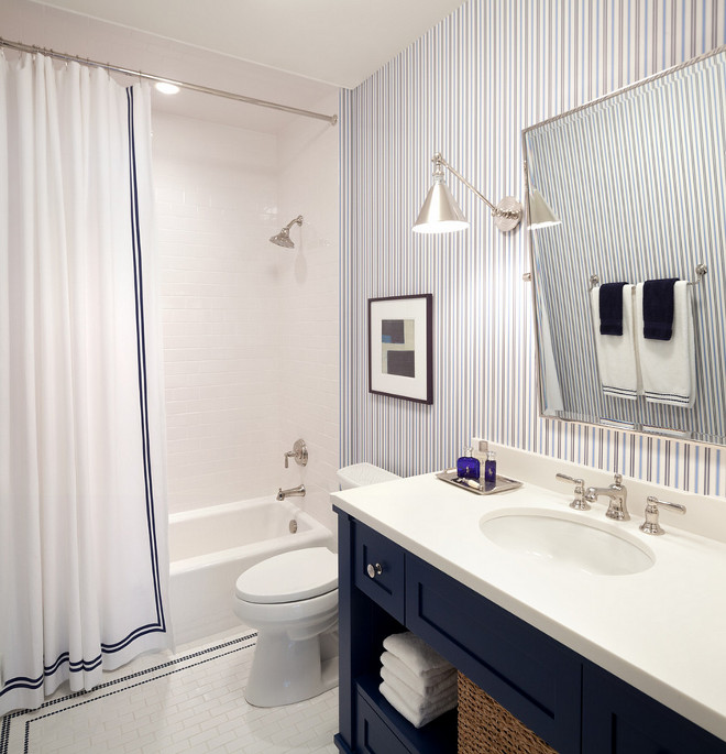 Blue and white bathroom with striped wallpaper. Blue and white bathroom with striped wallpaper and navy vanity with white countertop. #bathroom #blueandwhite #striped #wallpaper #navyvanity #blue #white #navycabinet #whitecountertop Kurt Baum & Associates.