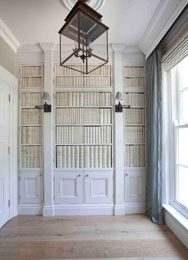 Foyer closet. Foyer closet ideas. This foyer is truly inspiring! The space features cabinet doors with faux ceramic books and sconces. The cabinet conceals a hidden closet. Lighting is Circa Lighting's Honore Hanging Lantern #foyer #closet #foyercloset #design #interiors Hayburn & Co.
