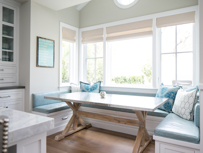 Breakfast nook. This breakfast nook is perfect for this family with small children. The table features stainless steel top on reclaimed wood trestle table base and the laminated fabric on the banquette is a mom's dream! #Breakfastnook #banquette #laminatefabric #table Churchill Design.