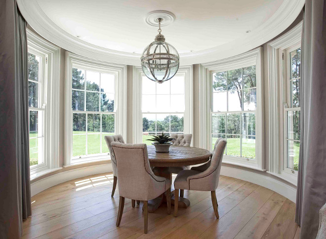 Breakfast room. Curved breakfast room. The curved sliding sash windows make a beautiful backdrop in this dining area. The curved windows are dressed in grays curtains with drapery hardware hidden behind built-in crown moldings. #breakfastroom #Curvedwindows #CurvedBreakfastroom Hayburn & Co.