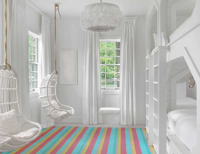 Bunk room with hanging chairs. All white bunk room with hanging chairs and colorful striped rug. #hangingchairs #bunkroom Amy Studebaker Design.