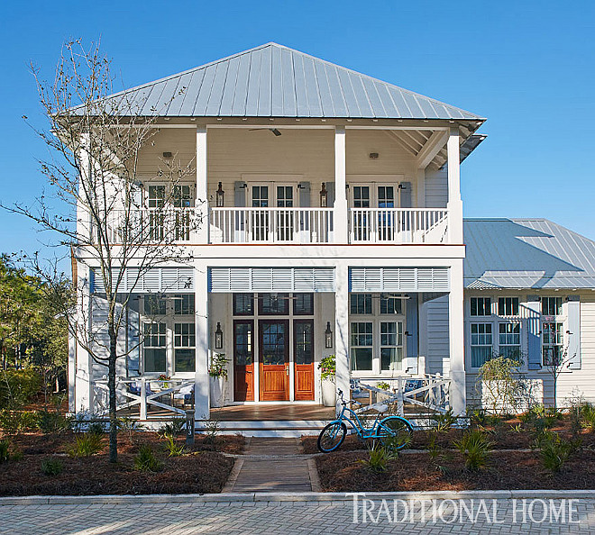 Florida Vacation Beach House. A two-level porch spans the front of the home. Florida Vacation Beach House Exterior #FloridaHome #VacationHome #BeachHouse. Traditional Home - T.S. Adams Studio.