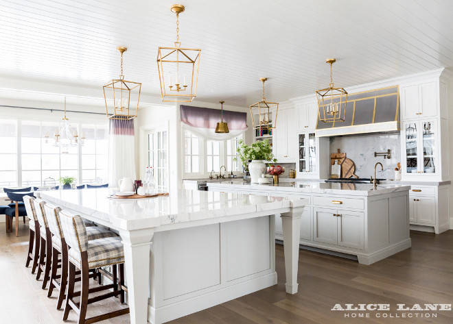 Ivory Lane Kitchen. A cook's kitchen features a white beadboard ceiling dotted with four Darlana 4 Light Lanterns illuminating two kitchen islands topped with white marble with one island designated for prep work and the other island designated for a dining table lined with gray check counter stools. A steel kitchen hood is accented with brass trim and stands over a marble cooktop backsplash lined with a swing arm pot filler and a stainless steel stove with dual ovens. A farmhouse sink fitted with aged gooseneck faucets is flanked by stainless steel dishwashers placed under windows dressed in a purple ombre roman shade illuminated by a Single Sloane Shop Light with Metal Shade. #kitchen #ivorykitchen #twoislands #IvoryLaneKitchen Alice Lane Home.