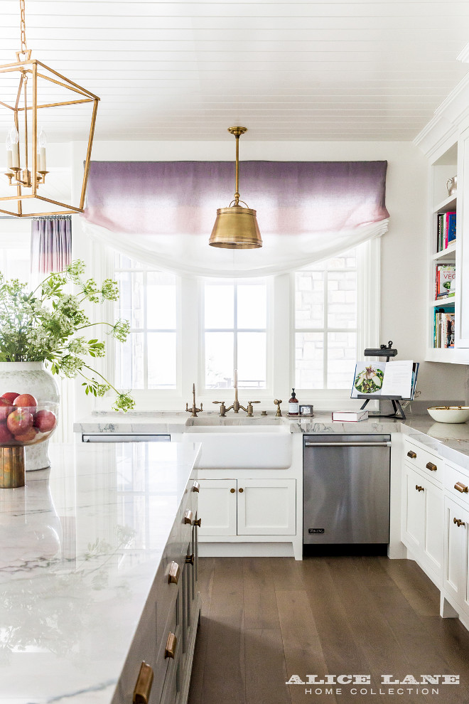 Kitchen Lighting. Brass Kitchen Lighting. Farmhouse Sink with Aged Brass Vintage Faucets Placed Under Antique Brass Drum Pendant Light. kitchen features a farmhouse sink fitted with aged gooseneck faucets is flanked by stainless steel dishwashers placed under windows dressed in a purple ombre roman shade illuminated by a Single Sloane Shop Light with Metal Shade. #kitchen #lighting #farmhousesink #kitchenlighting Alice Lane Home