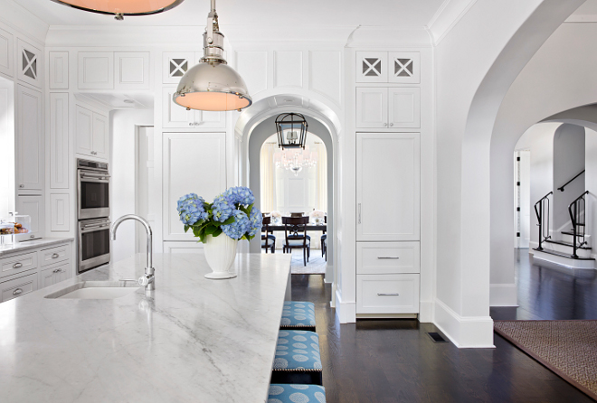 Two refrigerators in kitchen. This stunning white kitchen features a small prep sink on the island and white wood paneled refrigerators flanked by arched doorway. #tworefrigerators #kitchen #archway #arch TS Adams Studio Architects. Traci Rhoads Interiors.