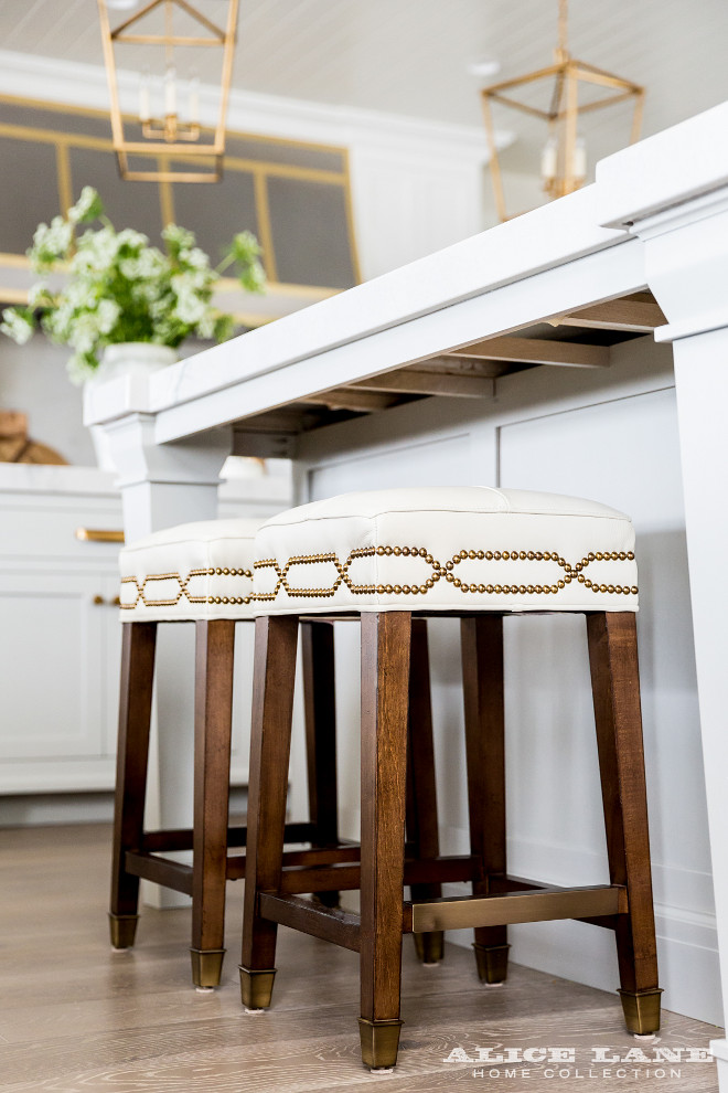 Kitchen stools. Kitchen features a white center island with legs lined with backless white counter stools with brass nailhead trim illuminated by Darlana Medium Lanterns in Antique Brass. #KitchenStools #stools #counterstools #barstools Alice Lane Home.