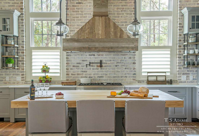 Kitchen with exposed brick backsplash, exposed brick walls and kitchen hood made of reclaimed wood planks. Kitchen cabinet paint color is SW Dorian Gray. TS Adams Studio Architects Inc.