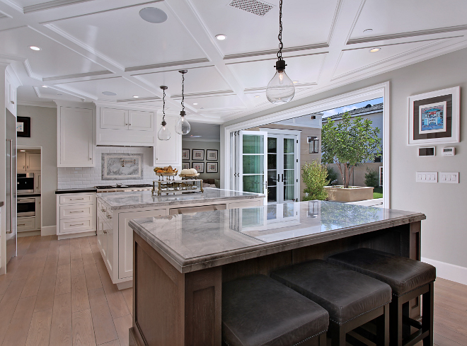 Kitchen with two islands and bifold doors to outdoors. One of the favorite features of the home is the open floor plan that flows into the yard and outdoor living space. Kitchen Island custom made from Rift Sawn White Oak with custom stain applied after installation. Kitchen Island Lighting: Restoration Hardware French Magnum 5L Pendant in Vintage Steel. Patterson Custom Homes