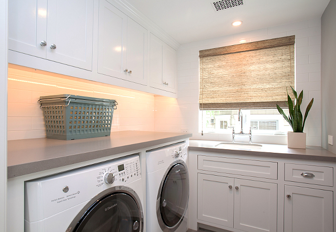 "Laundry Room. Laundry with white cabinets and gray walls painted in Benjamin Moore 1599 Marina Gray. Laundry room features Sleek Concrete #4003 Quartz countertop and 4"" x 16"" white subway tile as backsplash. #BenjaminMoore1599MarinaGray #BenjaminMoore #1599 #MarinaGray #BenjaminMoorePaintcolors Patterson Custom Homes"