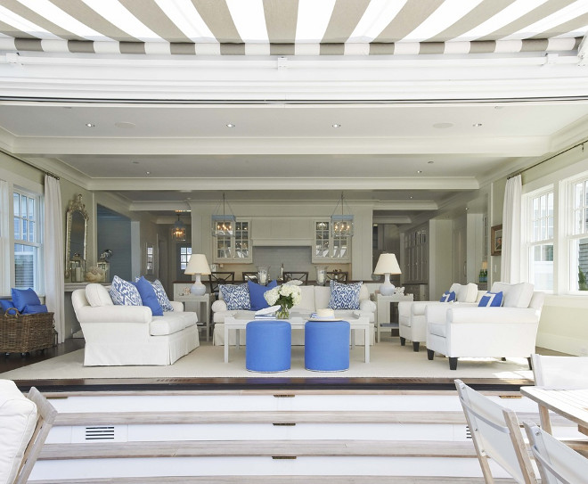 Living Room. White and blue living room features white roll-arm chairs adorned with blue border pillows facing white roll-arm loveseat across from white coffee table and round blue stools with silver nailhead trim atop white rug layered over espresso wood floors. A white roll-arm sofa is adorned with white and blue ikat pillows is flanked by gray end tables topped with ceramic lamps facing open doorway and steps leading to patio. Lynn Morgan Design.