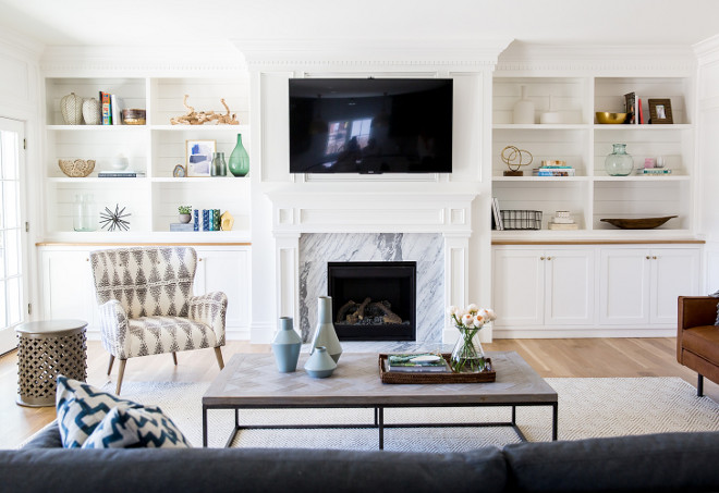 Living room cabinet. The living room is light and fresh with this fireplace with white marble and white cabinets with shiplap on shelves. #Livingroom #Fireplace #cabinet #shiplap Studio McGee.